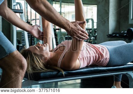 Woman With Her Personal Fitness Trainer Lifting Dumbell In Fitness Sport Gym