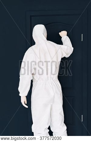 Man In Protective Medical Suit Knocking On Black Door. Virus Concept