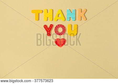 Thank You Inscription And Heart. Red Heart And Words Thank You Of Colorful Wood Letters On Yellow Ba