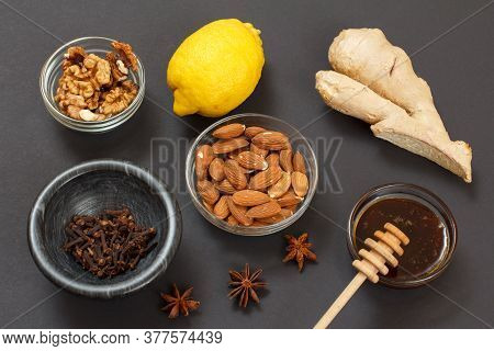 Health Remedy Foods For Cold And Flu Relief With Lemon, Ginger, Honey And Nuts On A Black Background