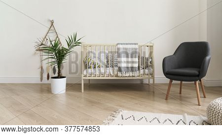 Cot Bed And Modern Gray Chair In Baby Bedroom
