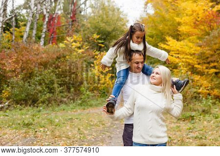 Picture Of Lovely Family In Autumn Park, Young Parents With Nice Adorable Daughter Playing Outdoors,