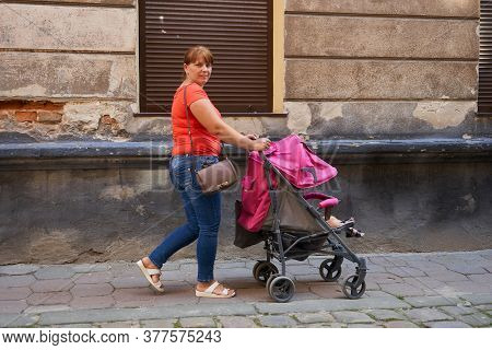 In The Old Town Woman With A Stroller, Walking Mom With Baby In A Sleeping Stroller