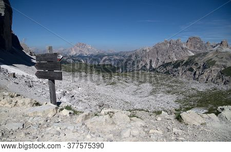 Signpost At The Foot Of The Italian Dolomites Overlooking The Mountains On A Background Of Blue Sky