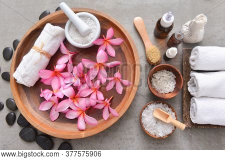 Composition of spa treatment with pink frangipani on gray background. Spa and wellness setting