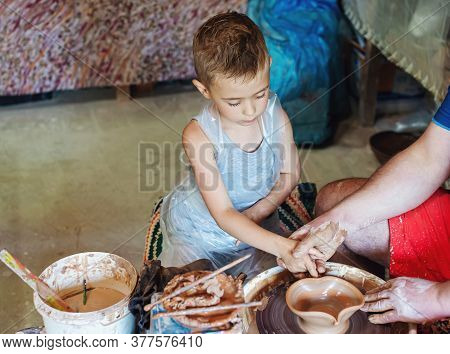 Small Child With Craftsperson Make Clay Bowl.