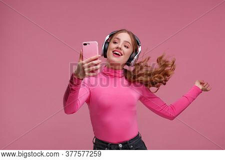 Enjoy Listening To Music. Beautiful Young Redhead Woman With Headphones Listening Music And Making S