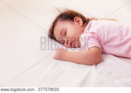 Adorable Innocent Little Girl Sleeping On Bed With Good Dream. Cute Mixed Race Infant Baby Feel Comf