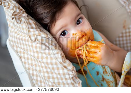 Adorable Little Toddler Girl Or Infant Baby Eating Delicious Spaghetti Food With Tomato Sauce On Bab