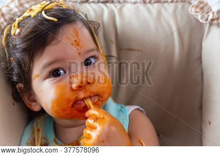 Adorable Little Toddler Girl Or Infant Baby Eating Delicious Spaghetti Food With Tomato Sauce. Funny