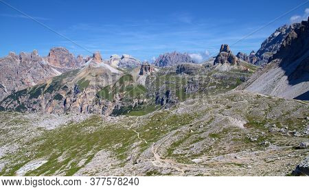 Mountain Path Running Along The Foot Of The Mountain Massif In The Italian Dolomites, Blue Sky Of Fl