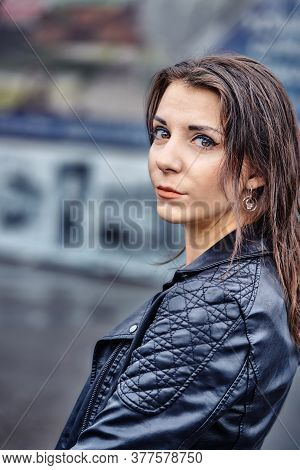 Portrait Of A Beautiful Brunette Girl In A Black Leather Jacket On A Cloudy Summer Evening. Close-up