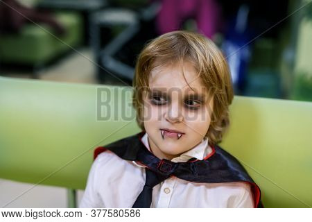 Cute Adorable Caucasian Kid Boy In Dracula Vampire Costume And Face Painting Makeup Sitting Indoors
