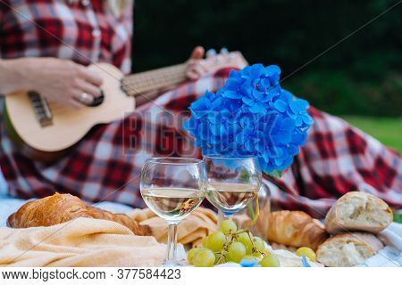 Girl In Red Checkered Dress And Hat Sitting On White Knit Picnic Blanket Plays Ukulele And Drinking