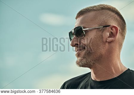 Portrait of a handsome brutal mature man with short hair and bristles wearing trendy sunglasses against the backdrop of a sky. Men's style. Optics for men.