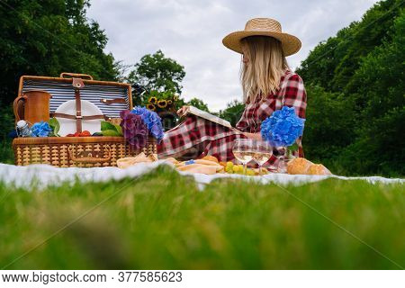 Girl In Red Checkered Dress And Hat Sitting On White Knit Picnic Blanket Reading Book And Drinking W