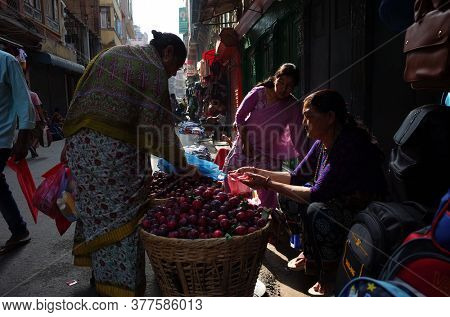 Kathmandu, Nepal - June 17, 2019: Local daily life on street, Nepali woman selling plum from big baskets on narrow street in old town