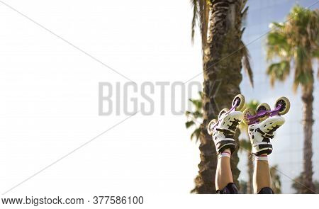 Girl's Legs Wearing Socks And Rollerskates Upside Down Against A Palm Trees In The Park. Space For T