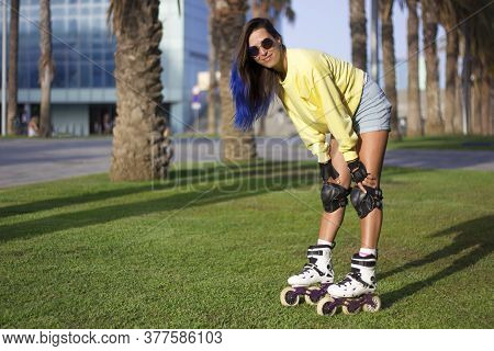 Young Girl On Roller Skates With Blue Hair And Sunglasses Standing And Resting On The Grass In The P
