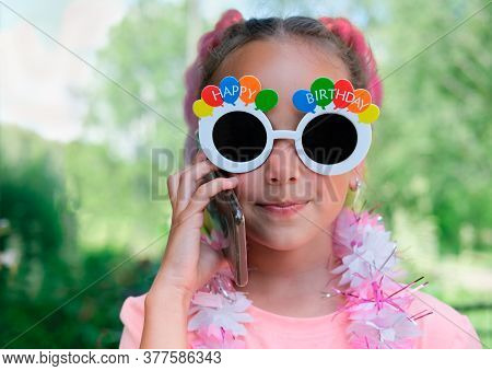 Beautiful Caucasian Girl Wearing Happy Birthday Sunglasses And Hawaiian Lei Garland. Girl Listening