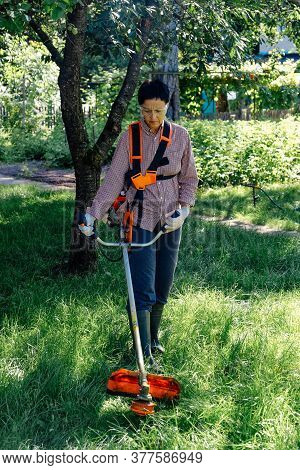 Female Worker Mowing Lawn With Grass Trimmer Outdoors In Garden.
