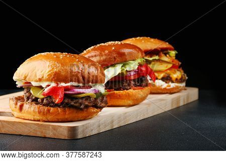 Set Of Three Burgers Close Up On Wood And Black Isolated Background For Copy Space. Big Tasty And Ju