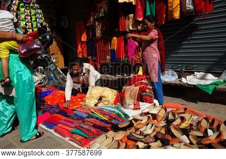 Kathmandu, Nepal - June 17, 2019: Selling colorful clothes and shoes on street market, Local daily life