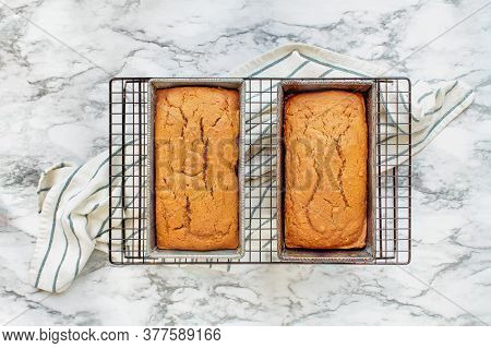 Two Freshly Baked Loaves Of Pumpkin Bread Resting On A Cooling Rack Over A White And Grey Marble Bac