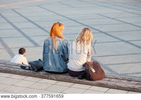 Novosibirsk, Russia - 07.03.2020: Two Friends Are Sitting On A Wooden Bench On The Steps On A Square