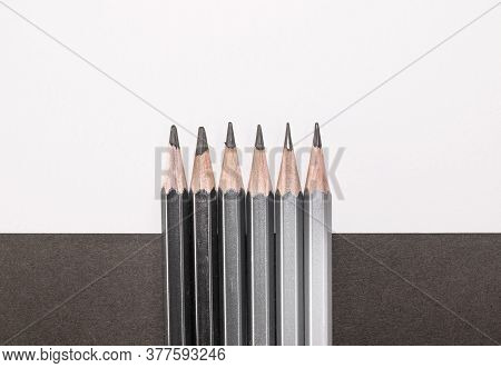 Row Of Dark Pencils On A Black And White Background, With Copy Space