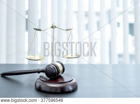 Judge Gavel, Scales Of Justice On The Office Desk, The White Background Office Of A Lawyer Or Judge.