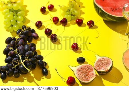 Grapes, A Bottle Of Wine And Different Fruits On A Yellow Background. The Concept Of Harvesting, Fun