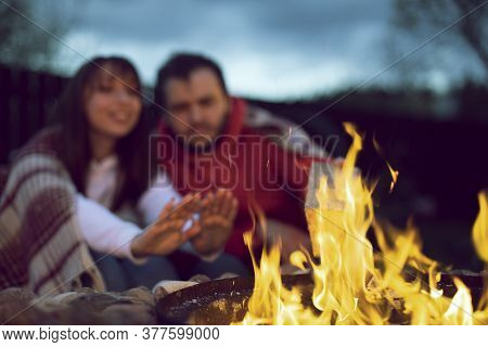 Portrait Of Happy Lovely Couple Sitting By Fire. Woman Warms Her Hands By The Fire. Relaxing Near Th