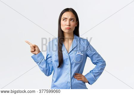 Pouting Disappointed Asian Girl In Blue Pajamas, Frowning And Sulking As Pointing Looking Upper Left