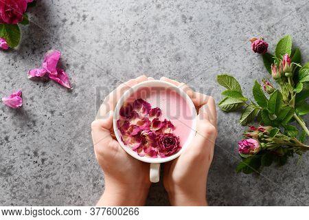 Rose Moon Milk In Child Hands On Grey. Top View. Ayurveda Warm Drink. Nice In Case Of Sleeplessness.
