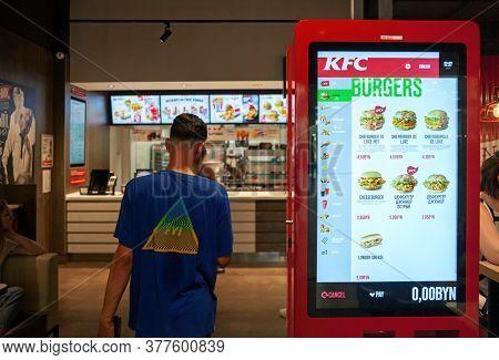 Minsk, Belarus, June 11, 2020: A Kiosk For Ordering Food In Kfc Restaurant. A Visitor Enters A Cafe.