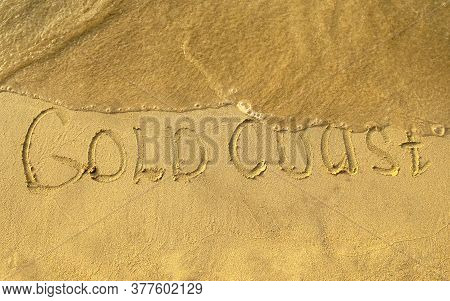 Gold Coast Words Written On Beach Sand With Water Wave. Gold Coast Inscription Is Written On A Sand.