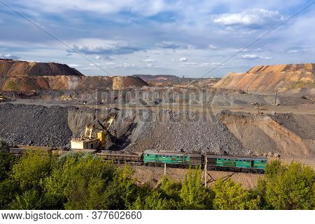Cargo Train Carrying Iron Ore On The Opencast Mining Quarry.