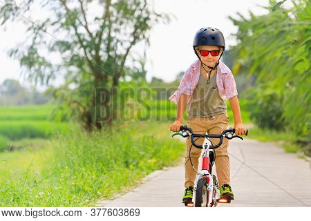 Country Cycling Walk. Young Rider Kid In Helmet And Sunglasses Riding Bicycle. Happy Child Have Fun