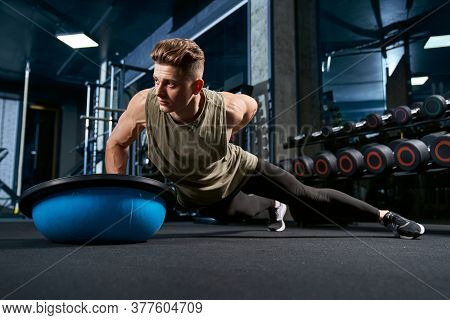 Front View Of Muscular Caucasian Man Doing Push Ups On One Hand On Floor Using Balance Half Ball. Cl