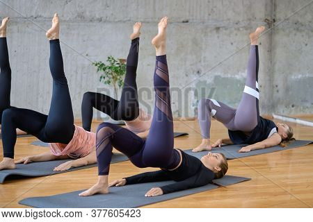Side View Of Group Of Sport Girls In Sportswear Working Out Yoga In Fitness Hall With Wooden Floor.