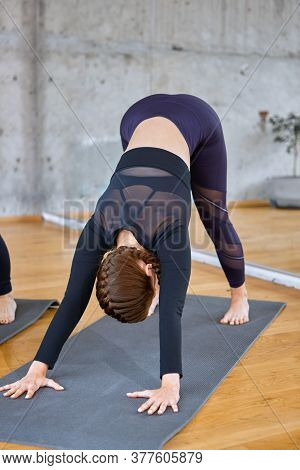 Front View Of Unrecognizable Young Sporty Woman Practicing Yoga Lesso, Stretching In Downward Facing