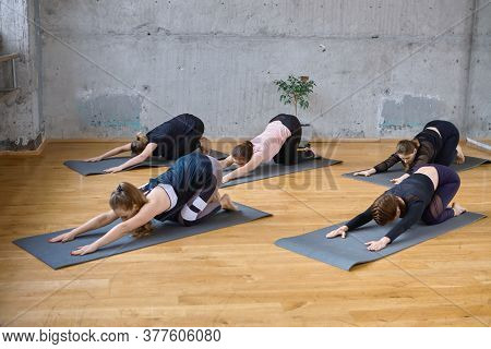 Group Of Five Sporty Women Practicing Yoga Lesson With Instructor, Doing Stretching Exercise On Mat