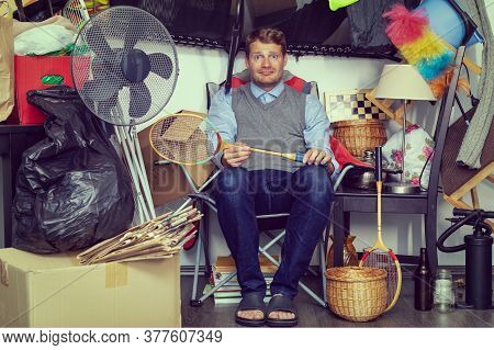 Compulsive Hoarding Disorder Concept - Man Hoarder With Stuff Piles Sitting In The Room