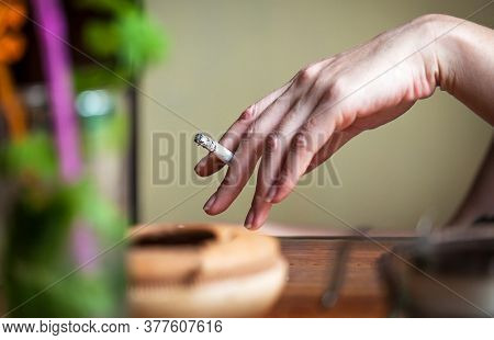 woman hand with a cigarette in a bar