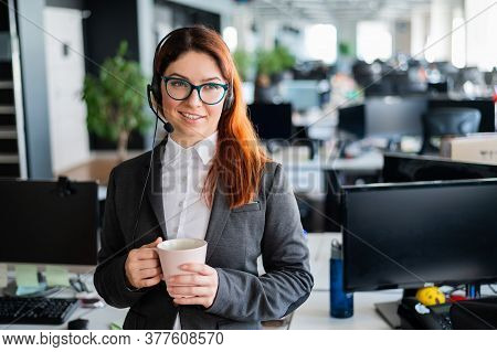 Happy Office Manager Wearing Glasses And Headset Holding Mug. Smiling Female Call Center Employee Is