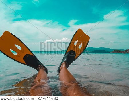 Women's Legs In Swimming Fins In The Aquamarine Tropical Sea. Hot Sunny Summer Tourist Season. Mount