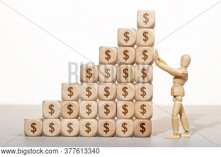 Growth, Wealth Or Richness Concept. Wooden Mannequin Holding A Pile Of Wooden Blocks Stacked With Do