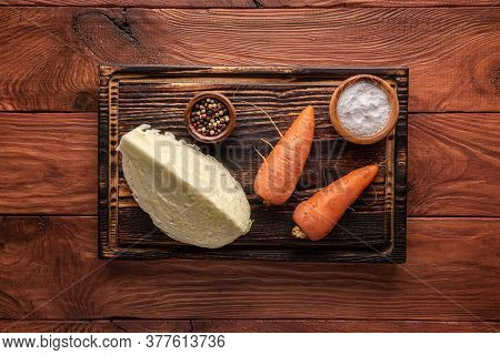Piece Of Cabbage, Unpeeled Carrots, Pepper And Salt On Wooden Cutting Board On Wooden Table Surface.