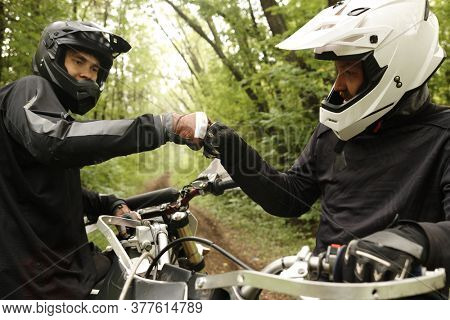 Male friends in helmets making fist bump while supporting each other, they enjoying motorcycling in forest